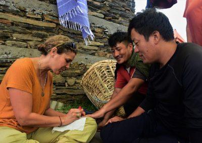 Helen Dobra painting the nails of some local men - HGA Women's Trek 2019