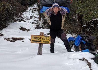 Porter trekkng to Nag Pokhari